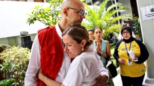 Canadian teacher Neil Bantleman, left, is hugged by his wife Tracy prior to the start of his trial hearing to listen to the prosecutor's demand at South Jakarta District Court in Jakarta, Indonesia, Thursday, March 12, 2015. (AP / Dita Alangkara)